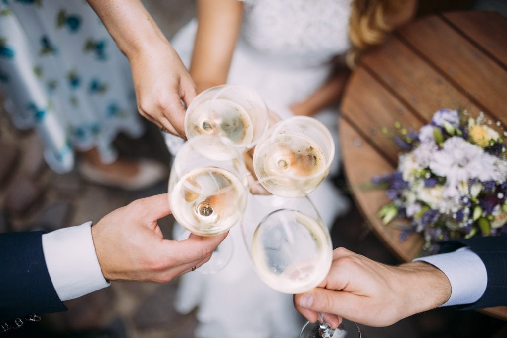 The Ultimate Wedding Photography Checklist Four people make a celebratory toast on a wedding day 9